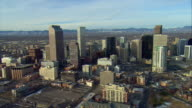 WS PAN ZO AERIAL View of downtown Denver with Rocky Mountains behind / Denver, Colorado, USA
