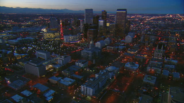 WS POV AERIAL View of downtown Denver with Rocky Mountains visible behind / Denver, Colorado, USA