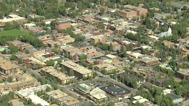 WS ZI AERIAL View of downtown tree lined streetscape with cars moving on down streets / Aspen, Colorado, United States