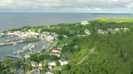 WS AERIAL View of downtown with buildings and port of boats / Mackinac Island, Michigan, United States