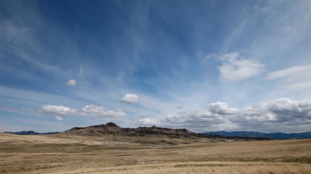 WS View of Dramatic clouds on prairie with Rockie Mountains in back side and sun and shadows rolling across landscape / Augusta, Montana, United States