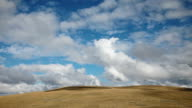 WS T/L View of Dramatic puffy clouds boiling over golden prairie hills / White Sulphur Springs, Montana, United States
