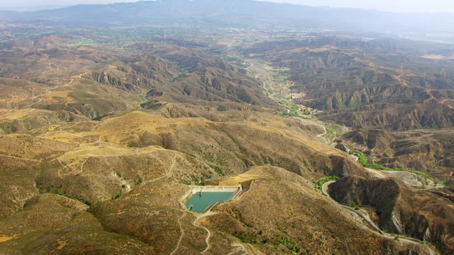 WS AERIAL POV View of Drinkwater Reservoir with road passing through brown hills / Los Angeles County, California, United States