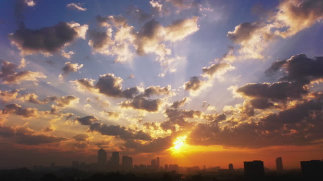 WS T/L View of Ealry morning sunburst though clouds over Canary Wharf city / London, United Kingdom