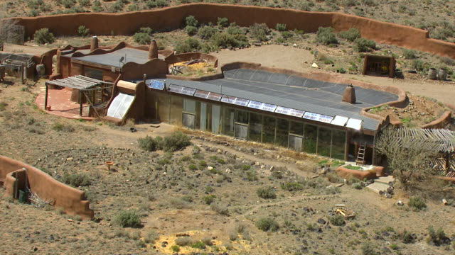 WS AERIAL View of Earthships houses with large solar panels and windows in Taos County / New Mexico, United States