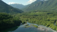 WS AERIAL View of Elwha river and forested valley in front of mountains / Washington, United States