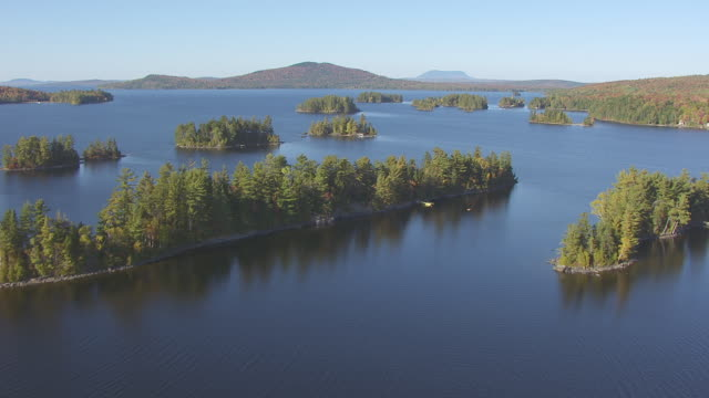 WS AERIAL POV View of fall forest with treetops and Moosehead Lake, mountain in background / Piscataquis County, Maine, United State