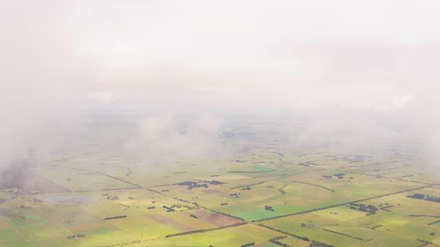 WS AERIAL View of farm field through clouds at wind farm / Melbourne, Victoria, Australia