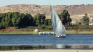 MS PAN View of felucca moving away behind sand bank and palms / Aswan, Egypt