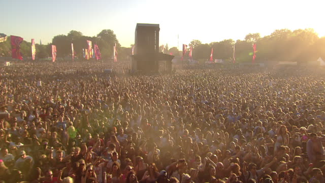WS POV View of Festival crowd in sun dancing with sitting on shoulders hands up in air / Victoria Park, London, United Kingdom