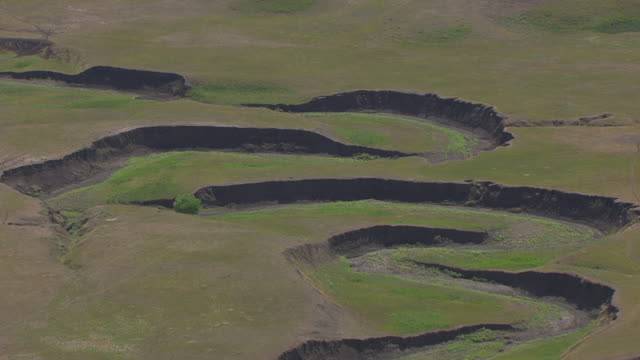 WS AERIAL TS View of fly by green dry river bed running through plains in Dewey County / Ridgeview, South Dakota, United States