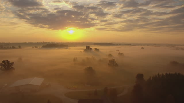 WS AERIAL View of fly over fields and approach farm during sunrise in Dodge County / Wisconsin, United States
