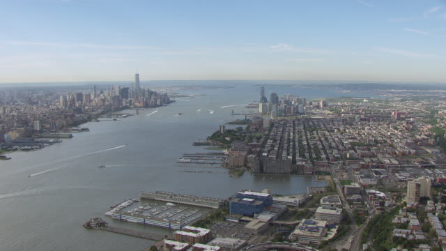 WS AERIAL View of flying over city with Hudson river and Manhattan in in distance / Jersey City, New Jersey, United States
