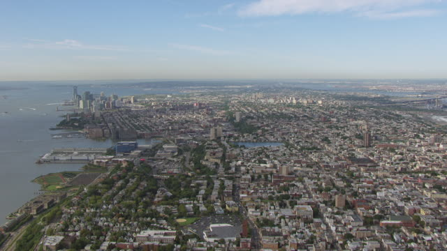 WS AERIAL PAN View of flying over Jersey city to Hudson river and Manhattan in in distance / Jersey City, New Jersey, United States