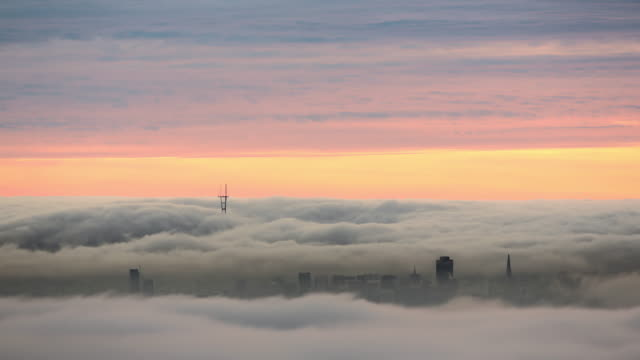 WS T/L View of Fog behind San Francisco skyline / San Francisco, California, United States