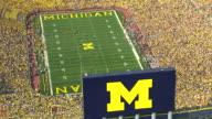 MS AERIAL ZO View of football players on field at Michigan Stadium during game / Ann Arbor, Michigan, United States