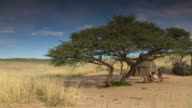 WS PAN View of Grassy landscape to people outside grass / straw hut, Boesmanland / North West Province, South Africa