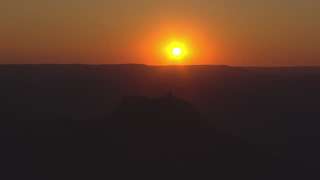 WS AERIAL View of Harney Peak Fire Tower against bright orange back side of sun set / South Dakota, United States