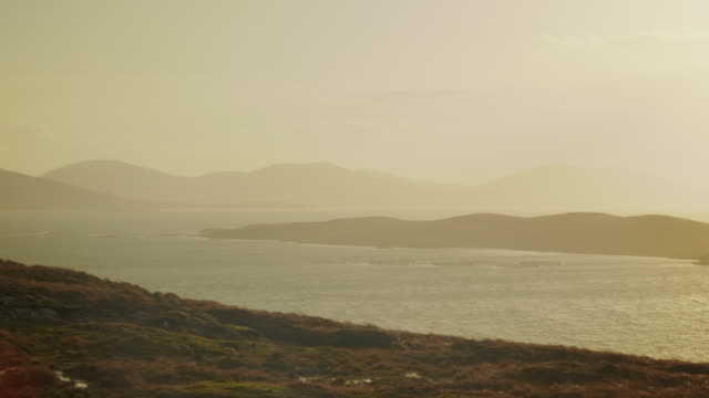 WS PAN View of harris island hills by sea with sun and clouds / Harris Island, Scotland, United Kingdom