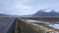 WS PAN View of highway going towards snowy mountain with reflection of snow mountain in lagoon / Iceland