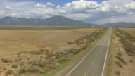 WS AERIAL TU View of highway leading to Rio Grande Gorge Bridge with car driving in Taos County / New Mexico, United States