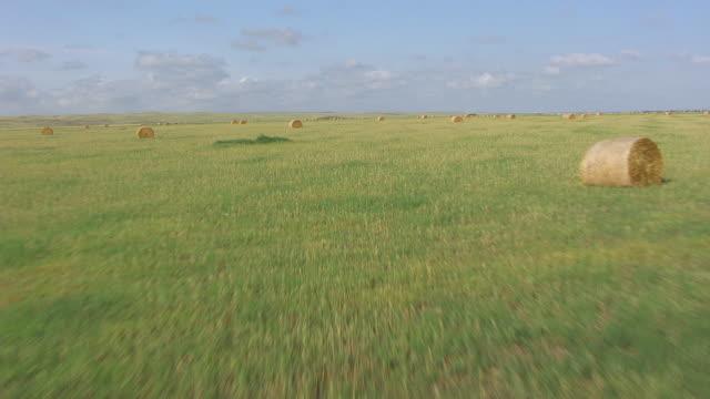 WS AERIAL View of hills along ground through hay barrels / Phillip, South Dakota, United States