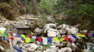 MS TU View of Himalayas creek runs past old mill with prayer flags hanging in / SoluKhumbu, Nepal