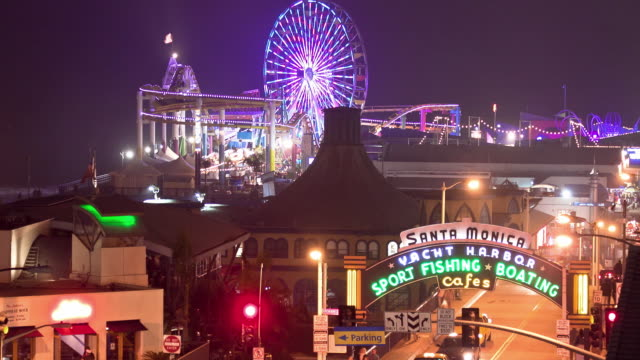 WS T/L View of historic Santa Monica Pier and Carousel built in the early 1900s with modern amusement park and roller coaster added below carousel / Santa Monica, California, USA