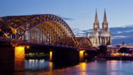 WS ZI T/L View of Hohenzollern Bridge with Cologne Cathedral and Rhine river at dusk / Cologne, North Rhine Westphalia, Germany