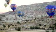 WS T/L View of Hot Air Balloons Rise over Goreme Town in Cappadocia / Goremel, Turkey