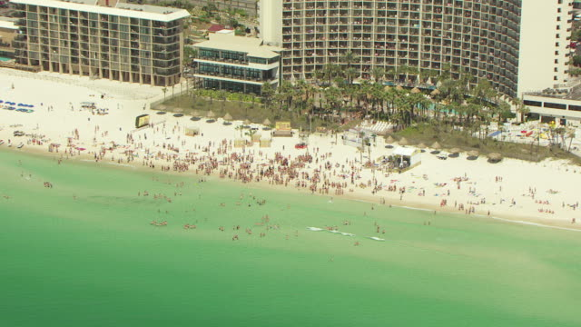 WS AERIAL ZI View of hotel and people on beach and spring breakers partying on beach / Panama City, Florida, United States