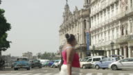 WS View of hotel Inglaterra with running vehicles on road and walking people / Havana, Cuba