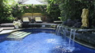 MS View of Hotel swimming pool with little waterfall at Asia / Candi, Dasa Bali, Indonesia