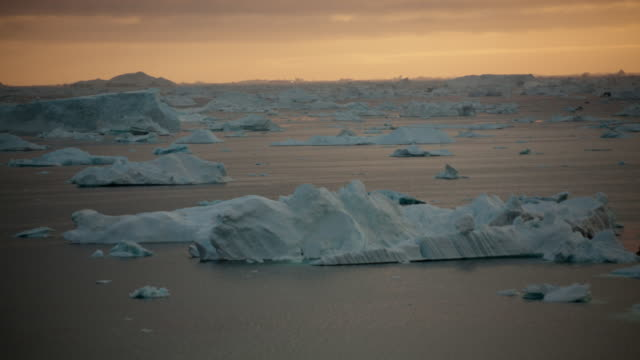 WS T/L View of icebergs moving in icy water at sunset with kayakers  / Ilulissat, Greenland