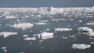 WS T/L View of icebergs moving in icy water / Ilulissat, Greenland