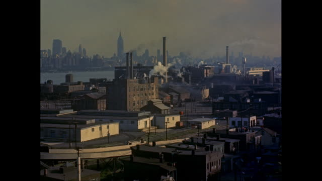 WS View of industrial buildings with New York City skyline in background /  New Jersey, United States