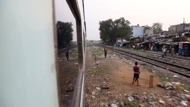 View of kids playing and Indian village from a train