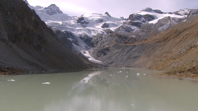 WS AERIAL View of lake vadret in front of roseg glacier and small pieces of floating ice in water with roseg glacier / Lake Vadret, Upper Engadin, Switzerland