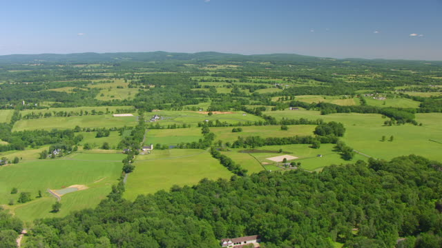 WS AERIAL POV View of landscape with farms against blue sky / Virginia, United States