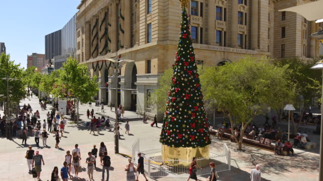 WS T/L View of large of people roaming around urban square with christmas tree in city / Perth, Western Australia, Australia