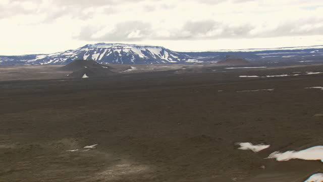 WS AERIAL View of Lava fields against snowy mountain / Iceland
