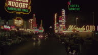 WS View of length of street in Las Vegas, people and vehicle traffic with neon lights on both sides