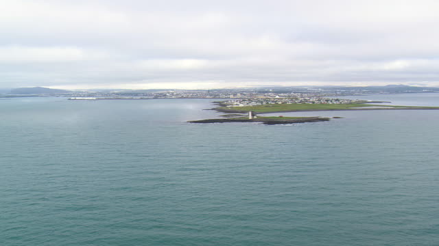 WS AERIAL View of lighthouse at island with Oskjuhlid city / Iceland