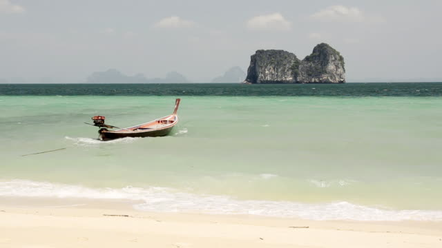 WS View of Long tail boat in Surf and Limestone rock in Sea, Marine National Park / Ko Hai, Krabi, Thailand