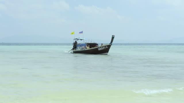 WS View of Long tail boat with Tourists reach beach, Marine National Park / Ko Hai, Krabi, Thailand