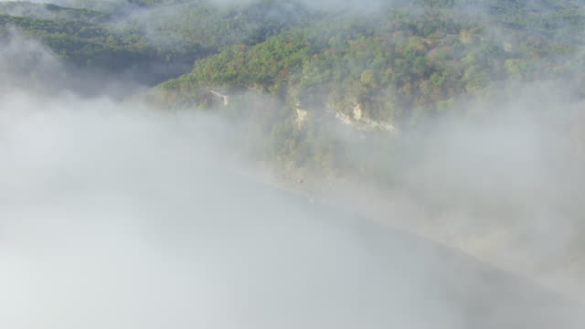 WS AERIAL View of low hanging clouds over water and forests in Prairie State Park in Barton County / Missouri, United States