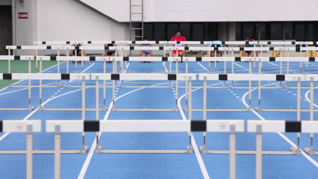WS View of Male runners jumping hurdles in race / Tokyo, Japan