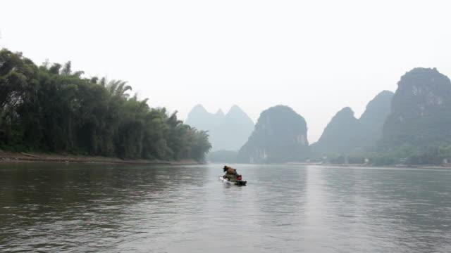 WS View of Man fishing with birds and river surroundings / Close to Li River, Guangxi, China
