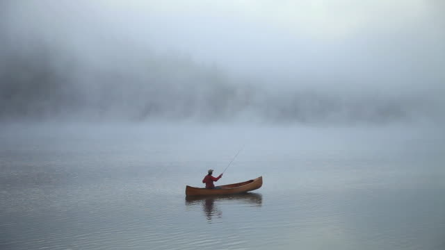 WS PAN View of Man in wood cedar strip canoe fly fishing on calm, misty, foggy mountain lake / Sealy Lake, Montana, United States