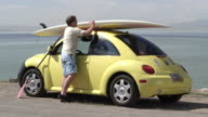 View of man shutting door to yellow car and grabbing surfboard off the top.